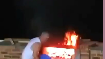 Man throws water on raging fire